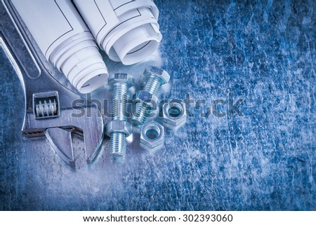 Steel adjustable spanner construction nuts bolts and rolls of blueprints on scratched metallic background maintenance concept.