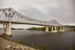 Steel and concrete bridge under stormy sky.  Bridge over the Mississippi River with rocks in the foreground.  Dark clouds over a scenic river.
