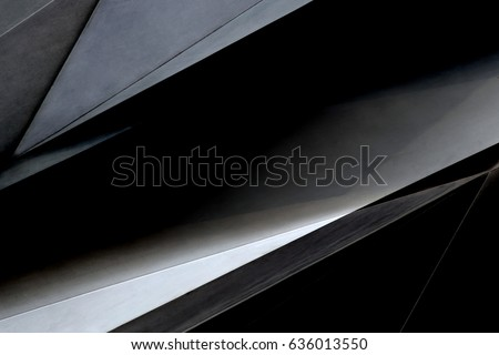 Steel and glass panels. Tilt close-up photo of office building fragment in darkness. Abstract background in black colors on the subject of modern architecture