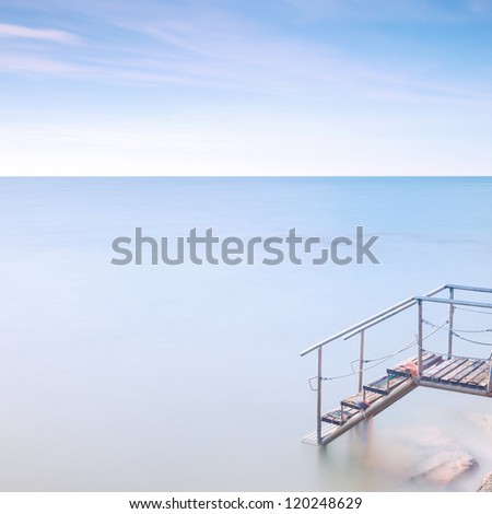 Steel and wooden old ladder pier in a cold atmosphere. Long exposure photography.