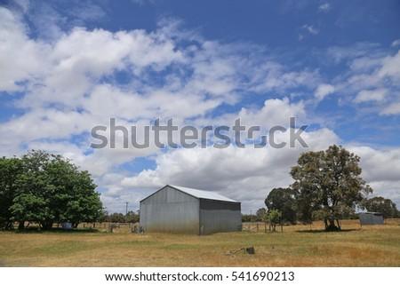 Steel barn on a farm with cloudy blue sky.
