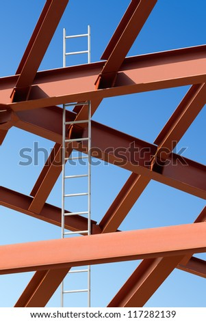 Steel beams and ladder against the blue sky. Fragment construction site. - stock photo