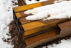 Steel beams stored outdoors are covered with rust, wet snow lies on them