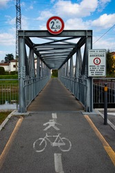 Steel bridge for bicycles and pedestrians in canal, italy