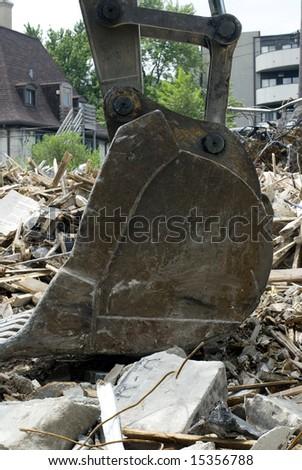 Steel bulldozer scoop resting on a demolished building.