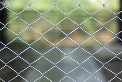 Steel cage mesh with green nature background.
