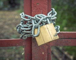 Steel chain and a lock or padlock on a metal gate or door.