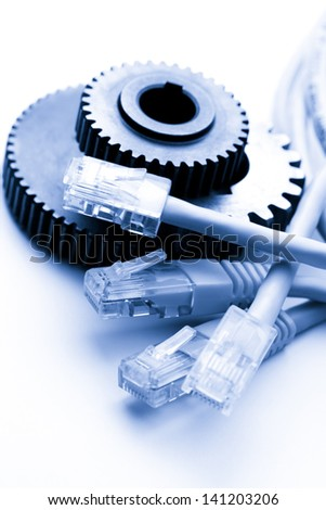Steel cogwheels and ethernet cable - stock photo