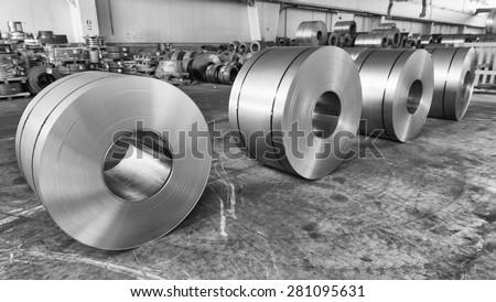 Steel coils inside industrial shed.