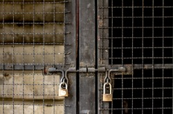 Steel door that separates the two sides light and dark with Old two rusty locks brass key lock