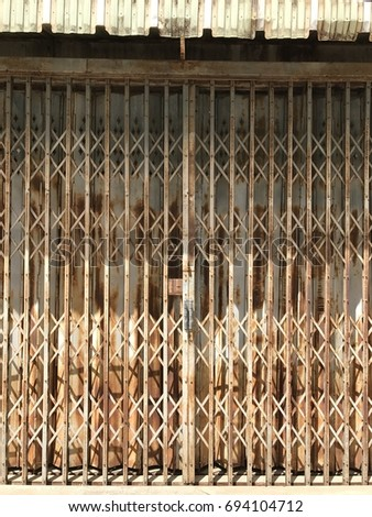 Steel door vintage and beautiful , Very old folding iron gate, warehouse entrance. #694104712
