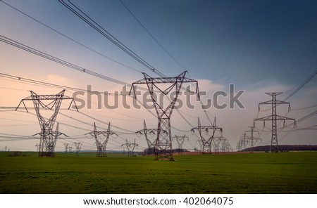 Steel electricity pylons of a power line on a green field