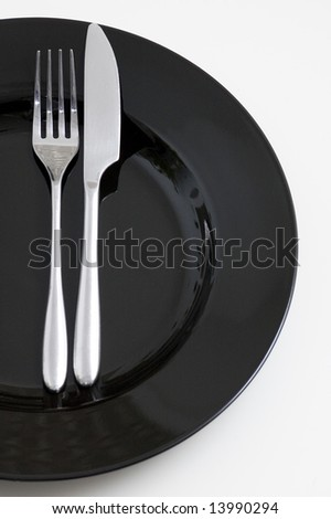 steel fork and knife on a black ceramic saucer isolated on white