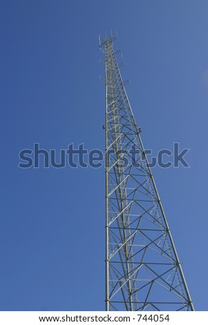 Steel frame tower against a blue sky. Tower is vertically framed and shot from below with plenty of open space for text.