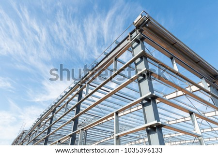 steel frame workshop is under construction against a blue sky #1035396133