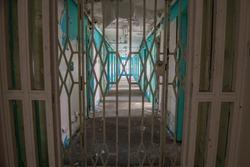 Steel gate across the corridor of prison cell doors inside an abandoned prison.