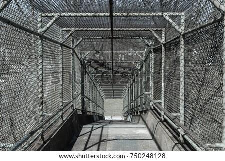 Steel gate walkway. Walkway bridge. Industrial design. Steel gate frame. Chain link fence. Abstract design. Industrial art. Light and shadow. Urban photography. Street photography.