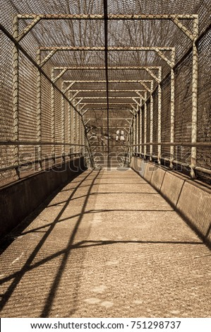Steel gate walkway. Walkway bridge. Industrial design. Steel gate frame. Chain link fence. Abstract design. Industrial art. Light and shadow. Urban photography. Street photography.