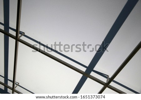 Steel girders and their shadows on white plastered ceiling background. Abstract modern architecture in minimalism office style. Minimal geometric background with polygonal structure of frames.