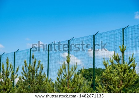 Steel grating fence made with wire on blue sky background. Sectional fencing installation