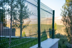 Steel grating fence of soccer field,Metal fence wire with bokeh in the background . Coiled razor wire with its sharp steel barbs on top of a wire mesh perimeter fence ensuring safety and security.