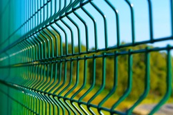 Steel grating fence of soccer field,Metal fence wire with grass in the background
