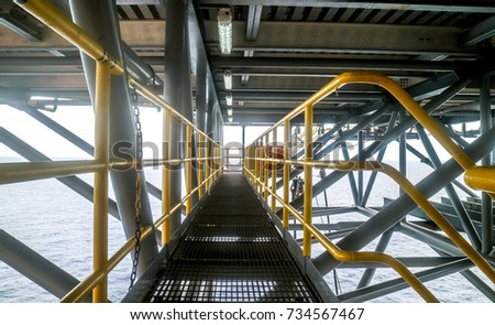 Steel grating walk way with yellow hand rail