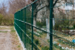 Steel grill. Green fence with wire. Fencing.