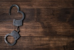 steel handcuffs on a wooden table with copy space. The idea of crime and punishment, the attacker, the court, the law. handcuffs top view gainst wood background for copy space
