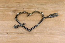 steel heart with arrow on wooden table, made of metal parts and bolts, front view. short focus