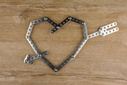 steel heart with arrow on wooden table, made of metal parts and bolts, top view