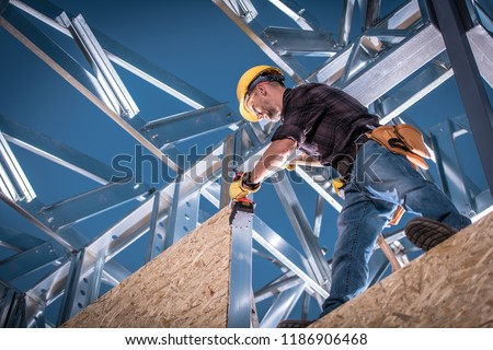 Steel House Constructor Worker. Caucasian Worker with Power Tool on the Building Frame.
