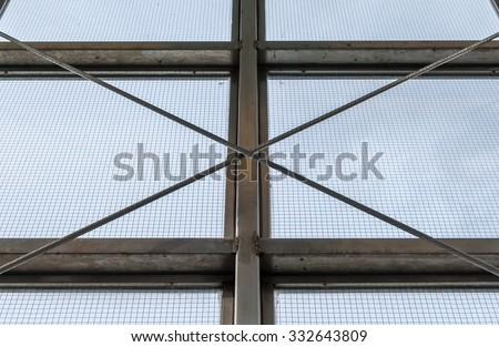Steel industrial window frame with steel cable support. Industrial window sill with screen and blue sky background. Urban geometrical design. Geometrical pattern interior architecture. Minimal design.
