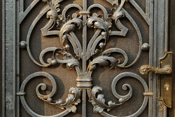 Steel, iron door for an ancient architectural background. The background of the metal door. Vintage color style. Entrance metal door to the house. Variety of old metal carpentry