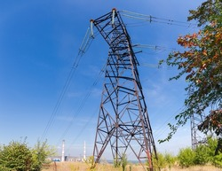 Steel lattice anchor transmission tower of overhead power line against the sky and distant thermal power station