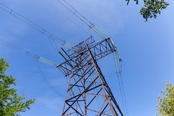 Steel lattice anchor transmission tower of overhead power line at the place of transmission line direction change, bottom view up against the sky