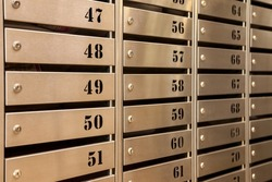 Steel Mailboxes in an apartment residential building. Even rows of numbered mailbox. Correspondence concept in city. You can use it as background for your creative. Copy space