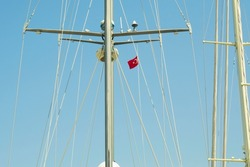 Steel mast with ropes and rigging   with navigation devices and sensors on a yacht against a blue sky in summer in Turkey