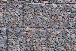 Steel mesh retain stones of gabion wall. Rockfall protection barrier. Gabion wall construction using steel wire mesh basket. Modern wall construction.