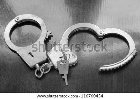 Steel metallic handcuffs with keys on wooden table
