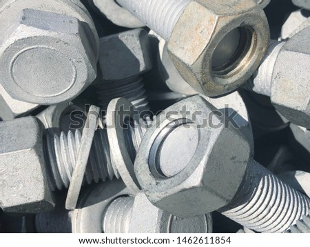 Steel nuts and screws piled in the box. Fastening construction equipment. Fixing hardware #1462611854
