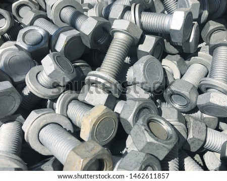 Steel nuts and screws piled in the box. Fastening construction equipment. Fixing hardware #1462611857