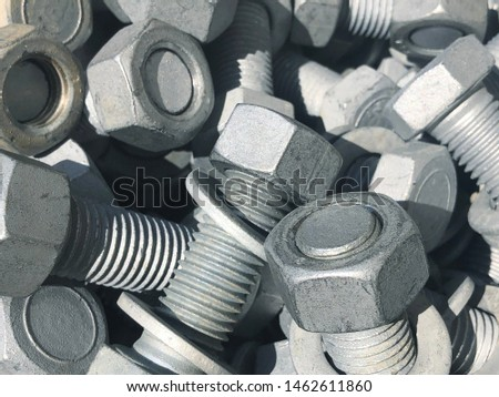 Steel nuts and screws piled in the box. Fastening construction equipment. Fixing hardware #1462611860