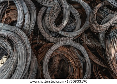 Steel piles, steel wires or coils for the construction industry Roll iron wire fence Wire coil for construction and industry Background of steel coil or steel.