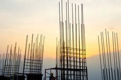 Steel reinforce in concrete column.Steel grid on the construction site.Reinforcement of concrete work. Using steel wire for securing steel bars with wire rod for reinforcement of concrete at sunset