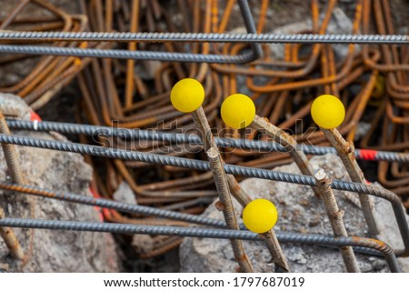 Steel reinforcement rebars with yellow protection caps. Covers protect workers from impalement on hazardous protruding metal thread bars rods used during construction pile process in building sites.  Сток-фото ©