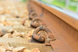 Steel retaining rails for tractors that are bent, reddish-brown color, because they are filled with iron rust. that was held on steel and railroad sleepers