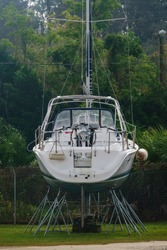 Steel rods hold a sailboat above ground for maintenance or storage in a coastal boatyard