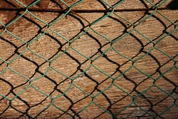 Steel rusty metal mesh on wooden background. Mesh pattern on the background of an old wooden wall. Green chain-link fence. Weathered and rusty old steel mesh as a background.