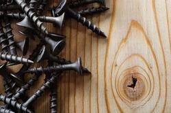 Steel screws on a wooden boards closeup